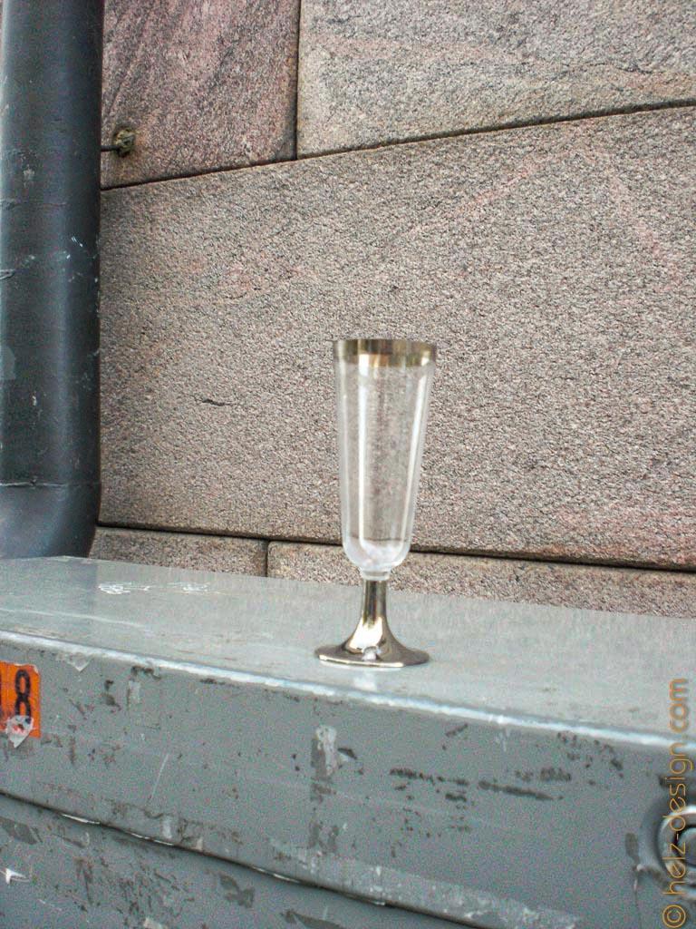 Ein einsames Sektglas auf einem Stromkasten