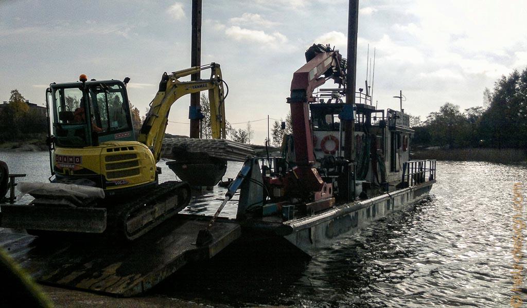 Ein Bagger fährt auf ein Boot
