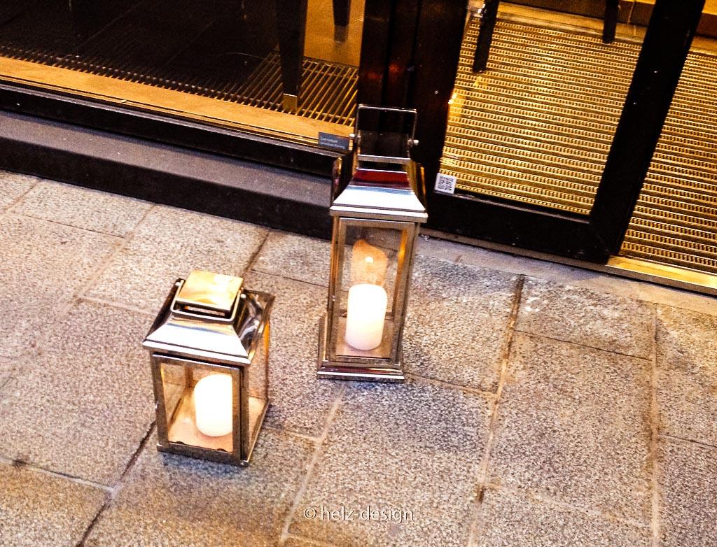 überall stehen so kleine und größere Windlichter mit brennenden Kerzen vor den Geschäften